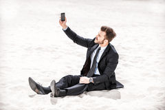 Poor signal. Frustrated young businessman searching for mobile phone signal while sitting on sand in desert royalty free stock photography