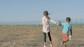 Small girl and boy refugees walk in desert towards fencing with barbed wire. Kid holds plush toy in his hand concept of forced imm. Poor small girl and boy stock footage