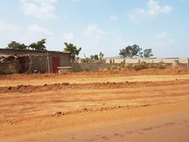 Poor streets of Bamako, Mali with red Arican soil. Generic poor street of Bamako, Mali with small houses near the red African soil highway Royalty Free Stock Image