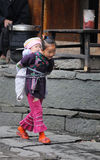 Poor traditional girl who care kid in the old village in China Stock Photography