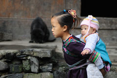 Poor traditional girl who care kid in the old village in China Stock Image