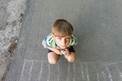 A poor and unhappy boy sits on the asphalt and asks for help while looking into the camera.  royalty free stock photo