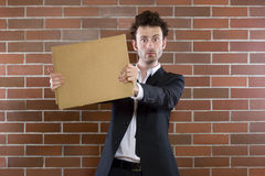 Poor unshaved businessman pleads with a blank sign Royalty Free Stock Images