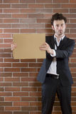 Poor unshaved businessman pleads with a blank sign Royalty Free Stock Image