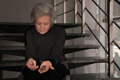 Poor upset mature woman with coins on stairs. Space for text royalty free stock photos