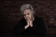 Poor upset woman sitting at table. Near brick wall stock image