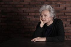Poor upset woman sitting at table near brick wall. Space for text stock photos
