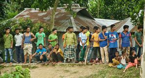 Village people standing on a road to watch a cricket match in Bangladesh. Poor villagers are standing around a road to watch the cricket match unique editorial royalty free stock photography