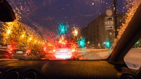 Poor visibility while driving car in Moscow. Poor visibility through wet windscreen while driving car on street in Moscow city in winter evening in snowfall Royalty Free Stock Image