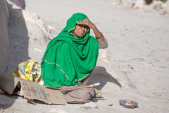 Poor woman begs for money from a passerby in Leh.  India. LEH, INDIA - SEPTEMBER 08 2014: An unidentified poor woman begs for money from a passerby in Leh Royalty Free Stock Photos