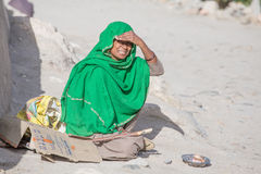 Poor woman begs for money from a passerby in Leh.  India. LEH, INDIA - SEPTEMBER 08 2014: An unidentified poor woman begs for money from a passerby in Leh Royalty Free Stock Images