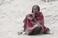 Poor woman begs for money from a passerby on the street in Leh, Ladakh. India. LEH, INDIA - JUNE 24, 2015: Unknown poor woman begs for money from a passerby on Stock Photography