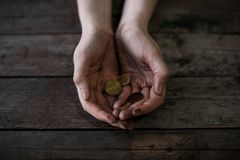 Poor woman with coins. On wooden background royalty free stock image