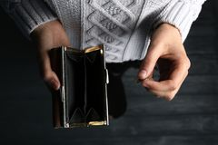 Poor woman holding empty wallet and coin. On wooden background, closeup stock images