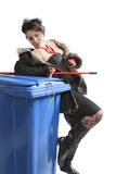 Poor woman near trash can Royalty Free Stock Image