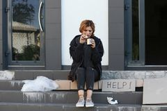 Poor woman with piece of bread and mug. On city street stock photography