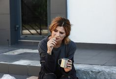 Poor woman with piece of bread and mug. On city street royalty free stock photography