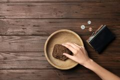 Poor woman with rye bread, wallet and coins at wooden table. Space for text stock image