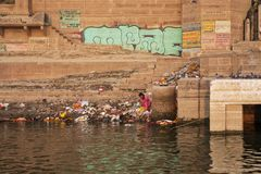 Poor woman sits on the banks of the Ganges river. Looking for so. Mething to eat in the garbage stock photography