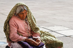 Poor woman sitting near church Royalty Free Stock Images