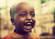 Poor young child laughing with tsetse insects on him. Tanzania, Africa Royalty Free Stock Image