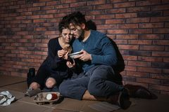 Poor young couple with bread on floor near wall. Poor young couple with bread on floor near brick wall stock photography
