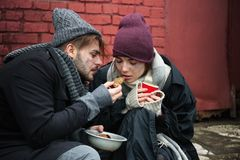 Poor young couple with bread on street. Poor young couple with bread on dirty street royalty free stock photography