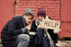 Poor young couple with HELP sign and bread on street. Poor young couple with HELP sign and bread on dirty street stock photography