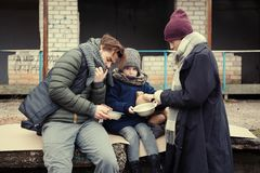 Poor young family with bread on street. Poor young family with bread on dirty street stock images