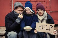 Poor young family with HELP sign on street. Poor young family with HELP sign on dirty street royalty free stock photos