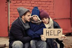 Poor young family with HELP sign on street. Poor young family with HELP sign on dirty street royalty free stock photography