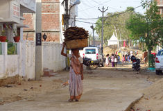 Poor young Indian woman hangind a basket on her head Stock Photography