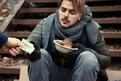 Poor young man begging for money on stairs outdoors. Closeup royalty free stock photos