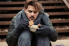 Poor young man with bread sitting on stairs. Outdoors stock photography