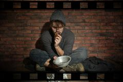 Poor young man eating bread on floor. Near brick wall stock images