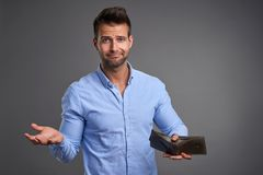 Poor young man. A poor handsome young man feeling stressed looking in to the camera and showing his empty wallet.r stock photo