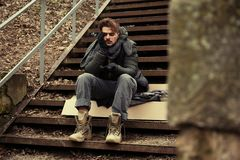 Poor young man sitting on stairs. Outdoors royalty free stock photos