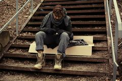 Poor young man sitting on stairs. Outdoors royalty free stock photography
