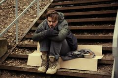 Poor young man sitting on stairs. Outdoors royalty free stock photo