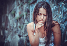 Poor young woman with a cigarette Stock Images