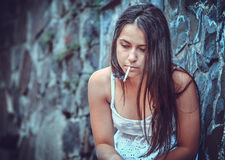 Poor young woman with a cigarette Royalty Free Stock Photo