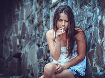 Poor young woman with a cigarette Royalty Free Stock Photography