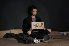 Poor young woman with HELP sign sitting on floor near wall. Poor young woman with HELP sign sitting on floor near dark wall stock photo