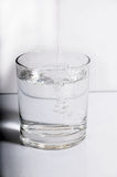 Pooring water. A glass of water.  Water is being pured in to the clear glass Royalty Free Stock Images