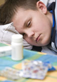 Poorly boy sleeping in bed. With medicine tablet bottle in foreground Royalty Free Stock Image