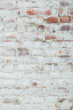 Poorly painted wall of damaged red brick with white paint, textu Stock Photos