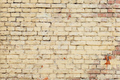 Poorly painted wall of damaged red brick with yellow paint, text Royalty Free Stock Images