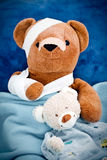 Poorly teddy bear. With bandaged head and arm under blankets with soft toy Stock Images