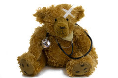 Poorly teddy with stethoscope. Cute teddy bear with plaster on head and stethoscope around neck, white background Royalty Free Stock Photography