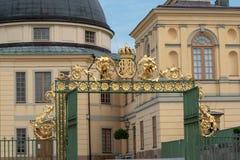 Poort met gouden koninklijk monogram bij Drottningholm-kasteel stock foto